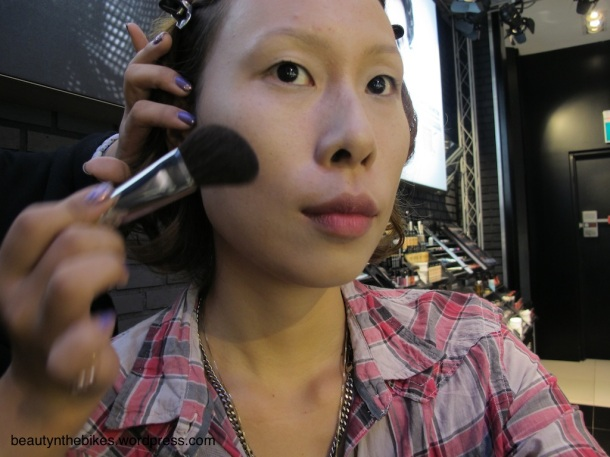 To contour my face, Amber demonstrates how to apply a sculpting powder under the cheekbones for better definition.