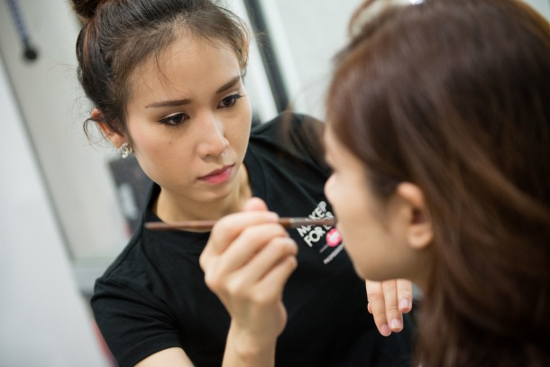 Demonstrating techniques on beauty makeup